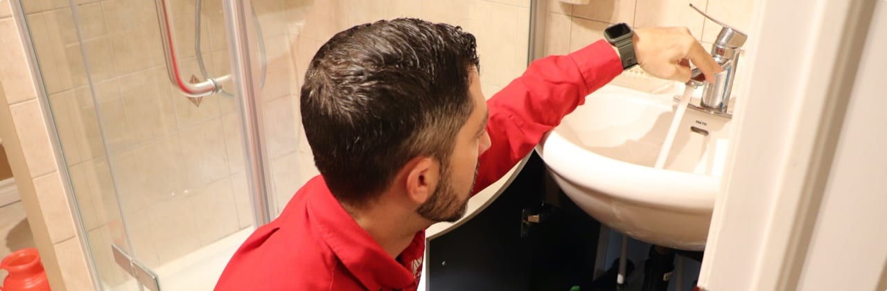 Atlas care worker in red uniform fixing faucet for bathroom sink